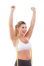 Worked off the excess weight happy young woman with measuring tape on her shoulders raising hands up and smiling while standing Royalty Free Stock Photo
