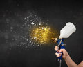 Worker with airbrush painting with glowing golden paint and particles Stock Image