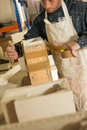 Worker assembling mold for plaster model a man in splattered clothing and sealing a with packaging tape Stock Image