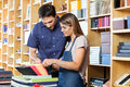 Worker assisting male customer to choose envelop mid adult female in shop Royalty Free Stock Image