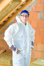 Worker attaching thermal insulation to roof in overall doing construction the with insulating material Stock Photo