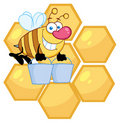 Worker bee carrying two buckets over honey combs Royalty Free Stock Photos