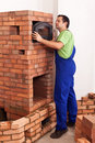 Worker building a masonry heater trying on and fitting the top oven door Royalty Free Stock Image