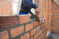 Worker building masonry house wal wall with bricks Stock Image