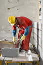 Worker Builds Cinder Block Wall - Vertical Stock Image