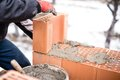 Worker buliding brick walls at house construction site, bricklayer Royalty Free Stock Photo