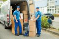 Worker with cardboard boxes in front of truck two happy male stack Royalty Free Stock Photography