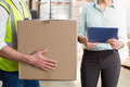 Worker carrying box with manager holding tablet pc Royalty Free Stock Photo