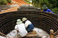 Worker casting cement culvert for road works workers by steel circular mould at mountain pass in lam dong viet nam in november Royalty Free Stock Photography