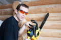 Worker with chainsaw in wooden house Stock Photos