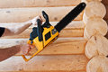 Worker with chainsaw in wooden house Royalty Free Stock Image