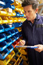 Worker checking stock levels in store room close up of Royalty Free Stock Image