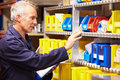 Worker checking stock levels in store room holding clipboard looking front of him Royalty Free Stock Image