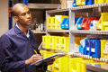 Worker checking stock levels in store room holding clipboard and pen Stock Photography