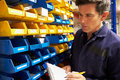 Worker checking stock levels in store room holding clipboard and pen taking notes Royalty Free Stock Photos