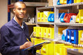 Worker checking stock levels in store room looking to camera smiling Stock Image
