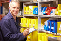 Worker checking stock levels in store room smiling at camera Stock Images