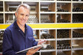 Worker checking stock levels in store room smiling to camera whilst holding clipboard Royalty Free Stock Photography