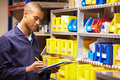 Worker checking stock levels in store room writing down information Stock Photo