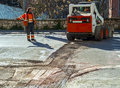 Worker checks traffic during the road surface milling work Stock Image
