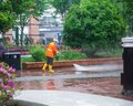 Worker cleaning driveway with high pressure washer splashing the dirt,professional cleaning services Royalty Free Stock Photo