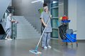 Worker cleaning floor with machine Royalty Free Stock Photo
