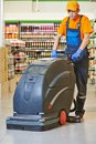 Worker cleaning store floor with machine care and services washing in supermarket shop Royalty Free Stock Photography