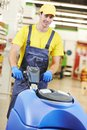 Worker cleaning store floor with machine care and services washing in supermarket shop Stock Photo