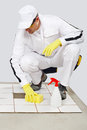 Worker cleans with sponge and spray old tiles Royalty Free Stock Image