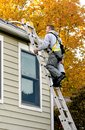 Worker climbing ladder to clean gutters Royalty Free Stock Photo
