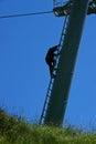 Worker climbing pole ski lift Stock Images