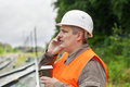 Worker with a coffee and cell phone on the railway Stock Photography