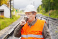 Worker with a coffee on the railway in summer Royalty Free Stock Photos