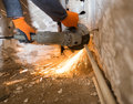 Worker cuts a metal pipe with sparks Royalty Free Stock Photo