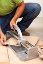 Worker cutting ceramic floor tiles closeup on cutter and hands Stock Photos