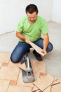 Worker cutting ceramic floor tiles and installing Stock Image