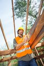 Worker cutting wood with handsaw at construction low angle view of male site Royalty Free Stock Photo