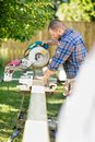 Worker cutting wood using table saw at site side view of mid adult manual construction Royalty Free Stock Images