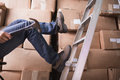 Worker falling off ladder in warehouse low section of the Royalty Free Stock Image