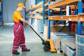 Worker with fork pallet truck Royalty Free Stock Image