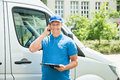 Worker in front of truck writing on clipboard young happy male Stock Photos