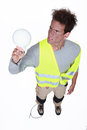 Worker getting an electric shock from a light bulb Royalty Free Stock Photo