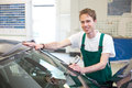 Worker in glazier s workshop installs windshield windscreen into car garage Royalty Free Stock Photo