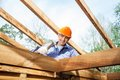Worker hammering nail on incomplete timber cabin low angle view of male at site Stock Images
