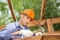 Worker hammering nail on wooden cabin male at construction site Stock Images