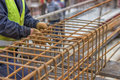 Worker hands fixing steel reinforcement bars at construction site Royalty Free Stock Photos