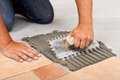 Worker hands spreading adhesive for ceramic floor tiles Royalty Free Stock Photo