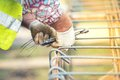 Worker hands using steel wire and pincers to secure steel bars preparing for concrete pouring on construction site Stock Images