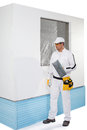 Worker holding a finishing insulation rasp near insulated wall Royalty Free Stock Photos