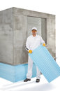 Worker holding an insulation panel in front of concrete wall Royalty Free Stock Images